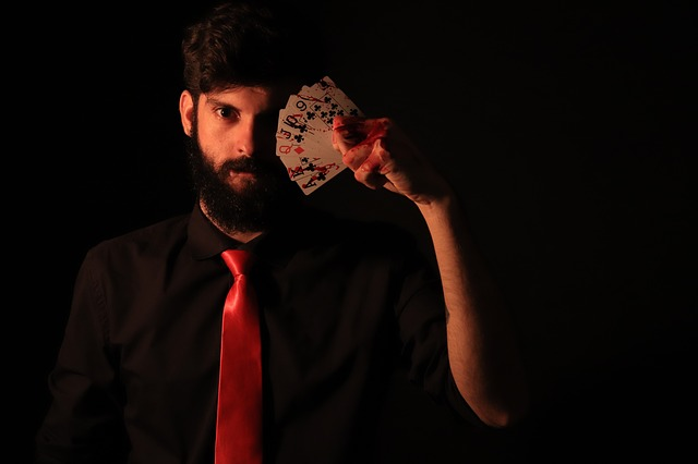 Mladý muž držící si před obličejem rozložené karty